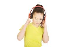 Mujer joven con los auriculares que escucha la música Fotos de archivo libres de regalías