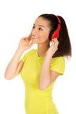 Mujer joven con los auriculares que escucha la música Fotos de archivo