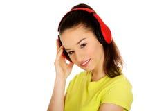 Mujer joven con los auriculares que escucha la música Imagenes de archivo