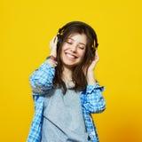Mujer joven con los auriculares que escucha la música Imágenes de archivo libres de regalías