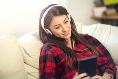 Mujer joven con los auriculares que escucha la música Fotografía de archivo libre de regalías