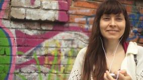 Mujer joven con los auriculares que escucha la música al lado de la pared con la pintada metrajes