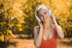Mujer joven con los auriculares que escucha la música en el parque en hierba, en otoño Fotos de archivo