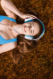 Mujer joven con los auriculares que escucha la música en el parque en hierba, en otoño Imagenes de archivo