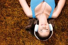 Mujer joven con los auriculares que escucha la música en el parque en hierba, en otoño Imágenes de archivo libres de regalías