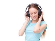 Mujer joven con los auriculares que escucha la música y el baile Fotos de archivo