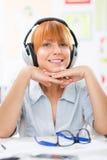 Mujer joven con los auriculares que escucha la música y que mira la cámara Imágenes de archivo libres de regalías