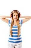 Mujer joven con los auriculares que escucha y que canta a la música, aislada en blanco Foto de archivo