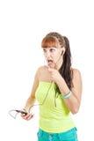 Mujer joven con los auriculares que habla con un amigo que usa el móvil Fotos de archivo libres de regalías