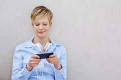 Mujer joven con los auriculares usando smartphone Imagen de archivo libre de regalías