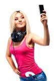 Mujer joven con los auriculares y el teléfono móvil Fotografía de archivo libre de regalías