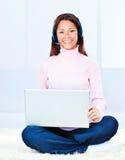 Mujer joven con los auriculares y la computadora portátil Fotos de archivo libres de regalías