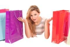 Mujer joven con los bolsos de compras que mienten en suelo Foto de archivo libre de regalías