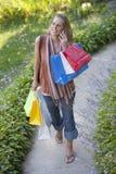 Mujer joven con los bolsos de compras y el teléfono celular Fotografía de archivo