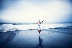 Mujer joven con los brazos aumentados por la playa Imágenes de archivo libres de regalías
