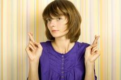 Mujer joven con los dedos cruzados Foto de archivo