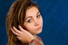 Mujer joven con los dreadlocks contra un fondo azul Fotografía de archivo