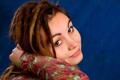 Mujer joven con los dreadlocks contra un fondo azul Foto de archivo