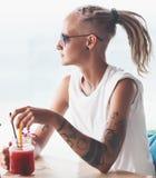 Mujer joven con los dreadlocks que se sientan en smoothie de consumición del café Fotos de archivo libres de regalías