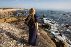 Mujer joven con los dreadlocks rubios que se colocan en rocas costeras hacia el océano Fotografía de archivo libre de regalías