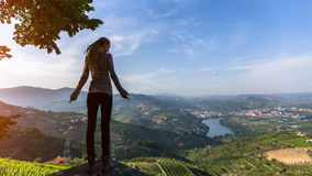 Mujer joven con los dreadlocks rubios que se retiran al borde de un acantilado y de miradas en el valle del Duero, Portugal Imagen de archivo