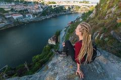 Mujer joven con los dreadlocks rubios que se sientan al borde de un acantilado y que miran el río abajo Fotos de archivo libres de regalías