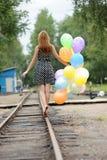 Mujer joven con los globos coloridos del látex Imagenes de archivo