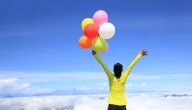 Mujer joven con los globos coloridos en pico de montaña Foto de archivo