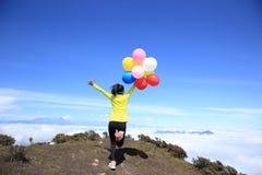 Mujer joven con los globos coloridos en pico de montaña Imagenes de archivo