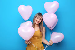 Mujer joven con los globos del corazón Imagenes de archivo