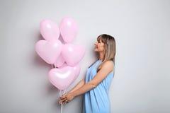 Mujer joven con los globos del corazón Foto de archivo libre de regalías