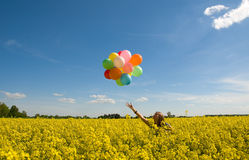 Mujer joven con los globos en campo del canola. Imágenes de archivo libres de regalías