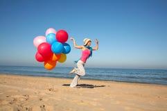 Mujer joven con los globos que se ejecutan en la playa Foto de archivo libre de regalías