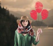 Mujer joven con los globos rojos Imagen de archivo