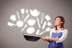 Mujer joven con los iconos de los accesorios de la cocina Imagen de archivo