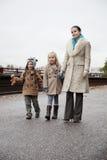 Mujer joven con los niños en ropa caliente que caminan junto en la calle Imagenes de archivo