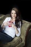 Mujer joven con los ojos azules hermosos que bebe el café Foto de archivo