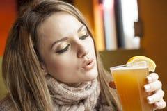 Mujer joven con los ojos azules hermosos que bebe la cerveza de Hefeweizen Fotos de archivo libres de regalías