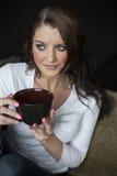Mujer joven con los ojos azules hermosos que sostienen la taza del café sólo Foto de archivo libre de regalías