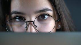 Mujer joven con los ojos de vidrios que miran detrás del monitor, cierre para arriba con la reflexión almacen de video