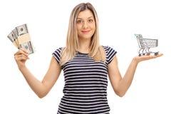 Mujer joven con los paquetes de dinero y de carro de la compra vacío Imagenes de archivo