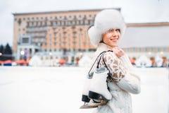 Mujer joven con los patines en manos en pista de patinaje Fotografía de archivo libre de regalías
