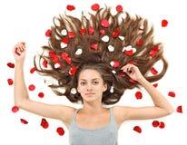 Mujer joven con los pelos largos y los pétalos color de rosa Imagen de archivo