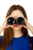 Mujer joven con los prismáticos Imagen de archivo