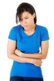Mujer joven con los problemas del estómago Imagenes de archivo