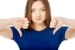 Mujer joven con los pulgares abajo Imagen de archivo