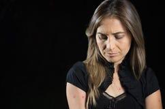 Mujer joven con los puntos rojos en sus brazos después de mordeduras de un mosquito, en un fondo negro Foto de archivo libre de regalías