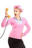Mujer joven con los rodillos del pelo que grita en un teléfono Fotografía de archivo libre de regalías