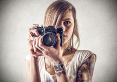 Mujer joven con los tatuajes que celebran una cámara Fotografía de archivo libre de regalías