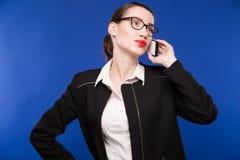 Mujer joven con los vidrios que habla en el teléfono Imagen de archivo